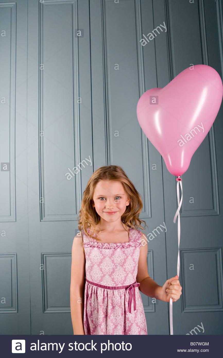kleines Mädchen in der Partei Kleid Rosa herzförmige Ballons halten ...