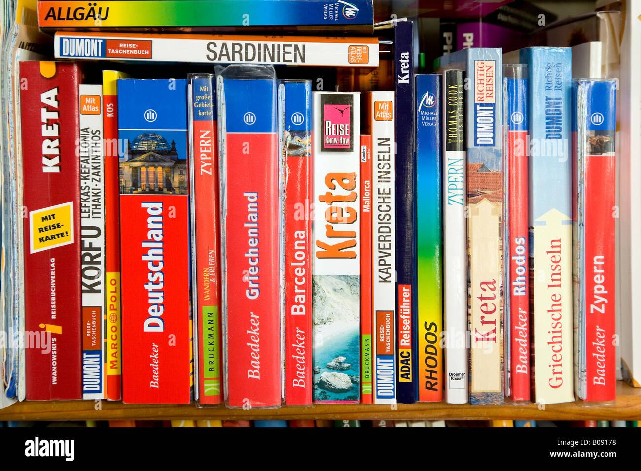 Verschiedene Reiseführer auf einem Bücherregal Stockbild