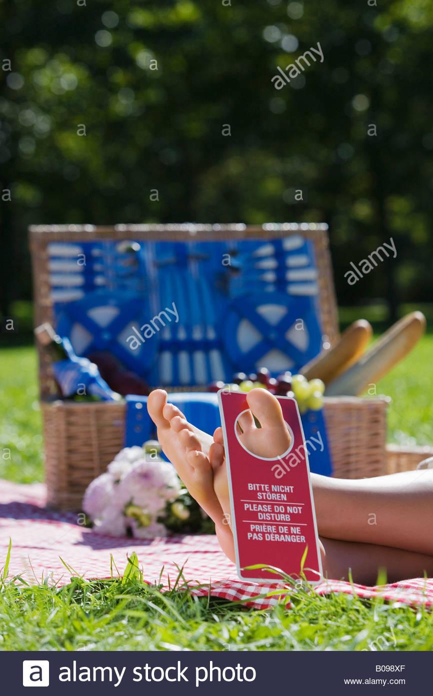 Picknick-Szene mit Frau liegend auf Decke mit Do Not disturb Schild auf ihren Zeh Stockbild