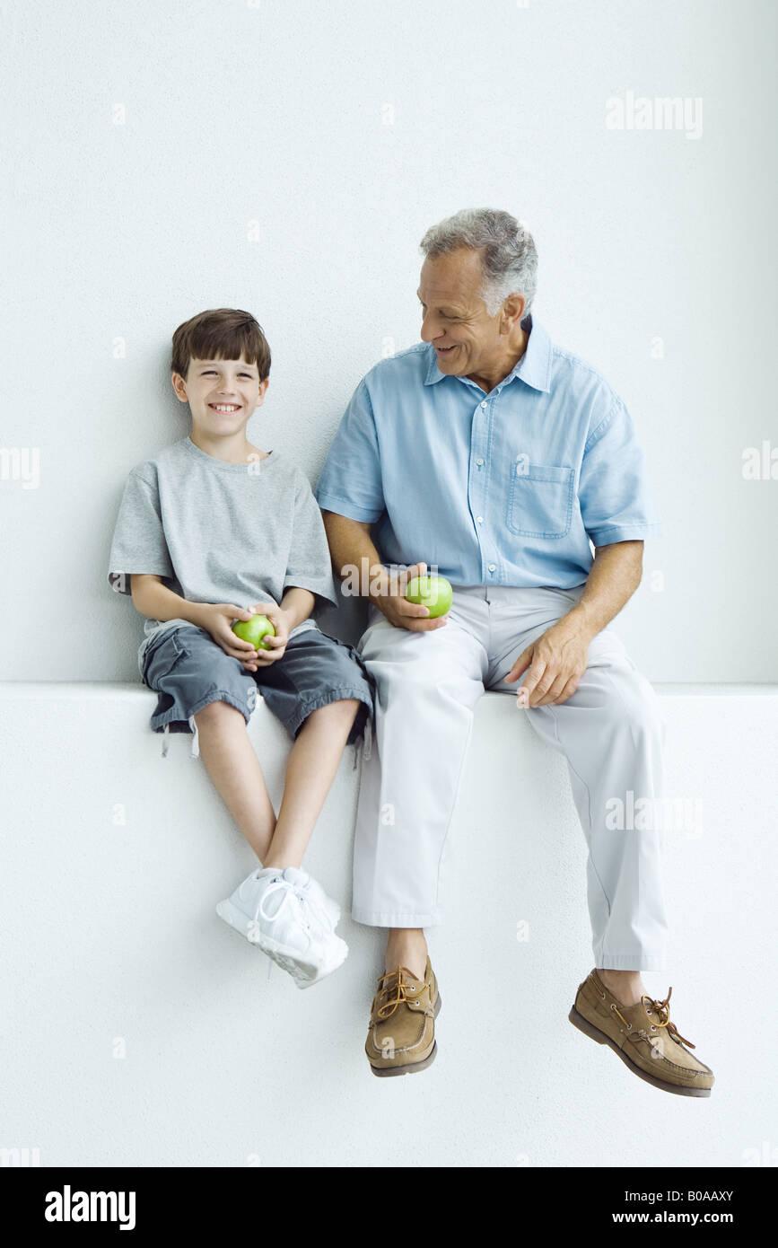 Großvater und Enkel sitzen nebeneinander auf Sims, Äpfel, beide Lächeln auf den Lippen halten Stockbild