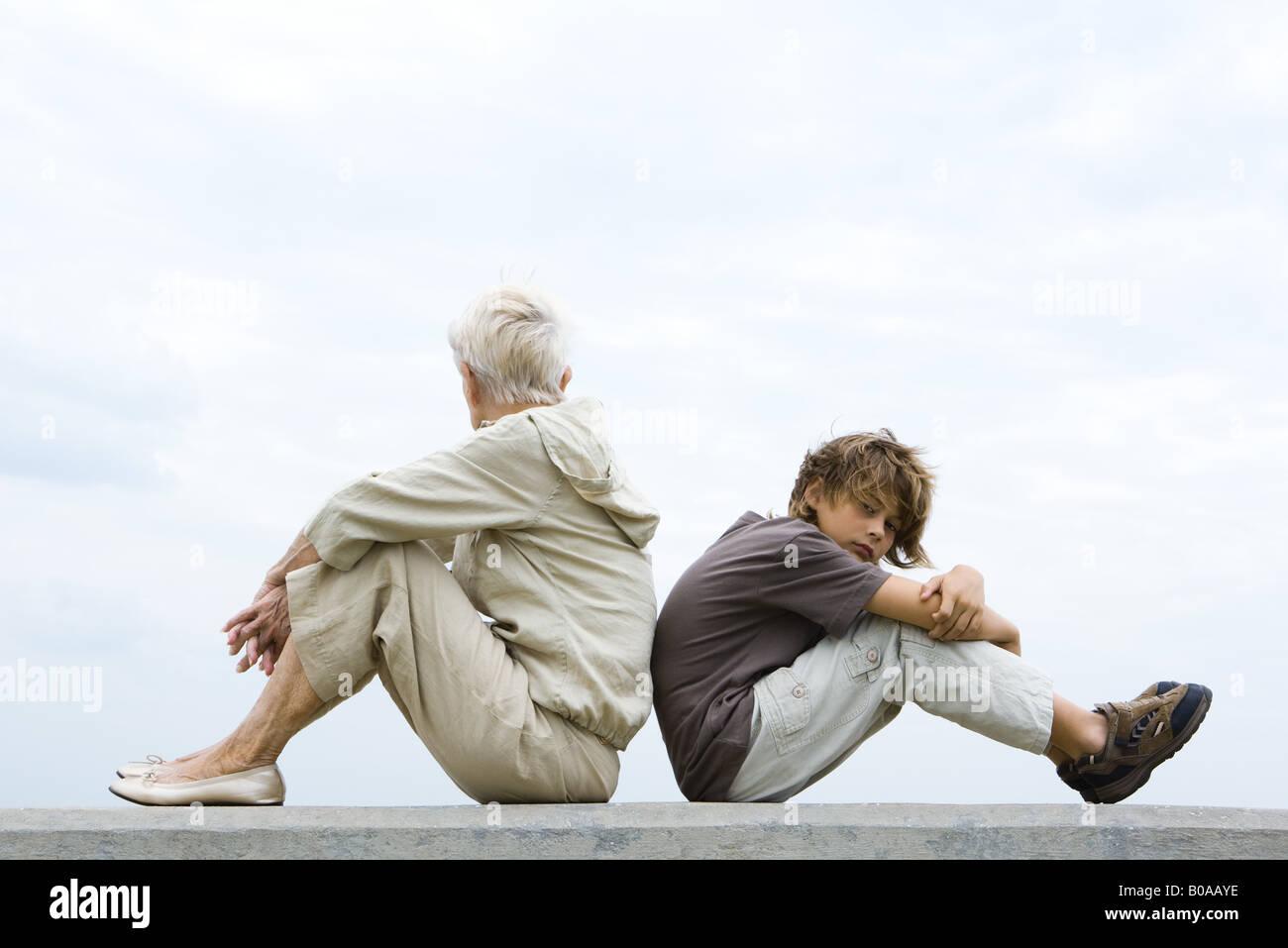 Großmutter und Enkel sitzen Rücken an Rücken, Frau Weg, junge Blick in die Kamera schauen Stockbild