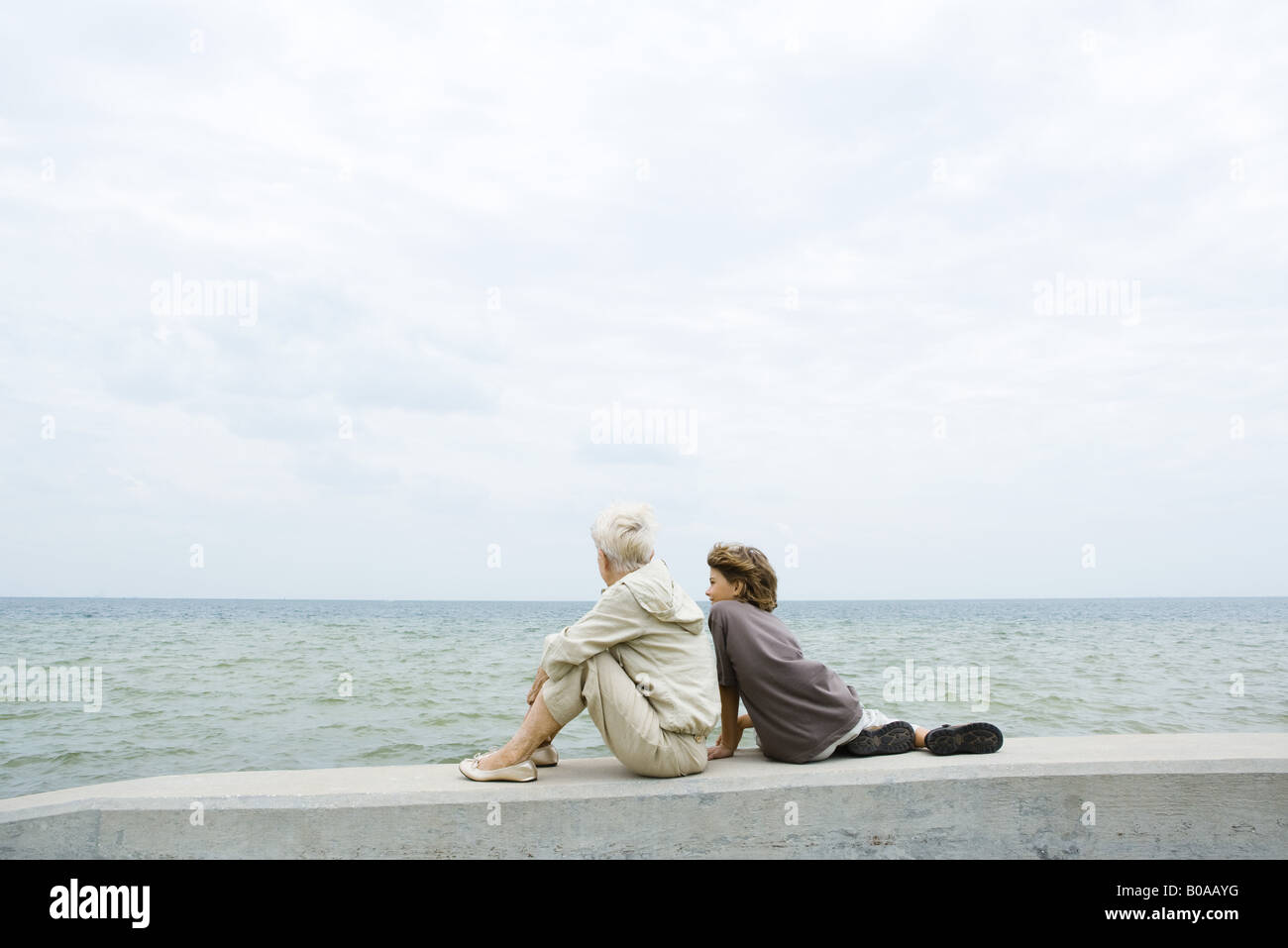 Großmutter und Enkel sitzen zusammen durch das Meer betrachten, Rückansicht Stockbild
