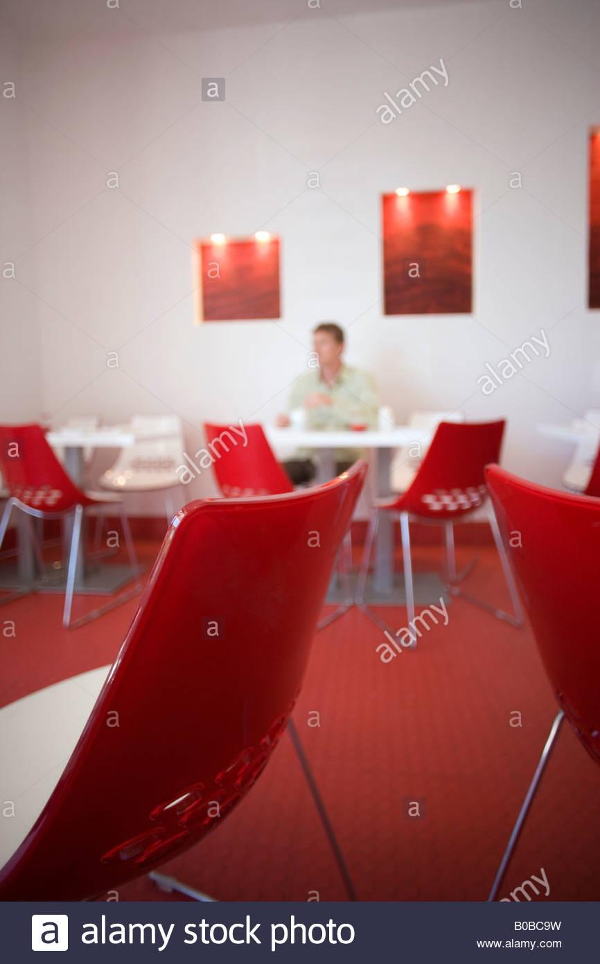 Mann, sitzend am Tisch im modernen Café mit roten und weißen Dekor, Fokus auf Tisch und Stühle im Vordergrund Stockfoto