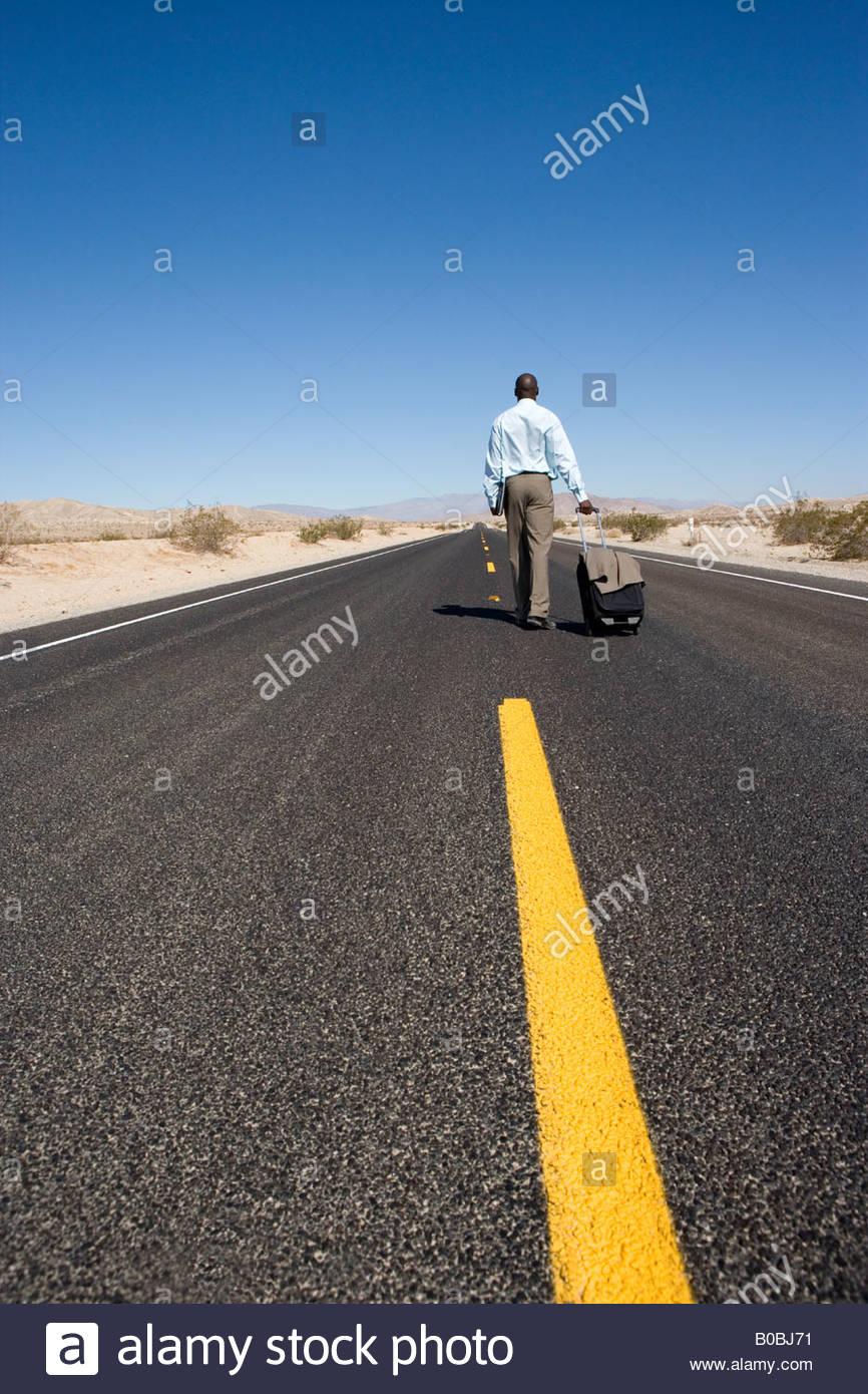 Geschäftsmann mit Gepäck unterwegs in der Wüste, Rückansicht Stockfoto