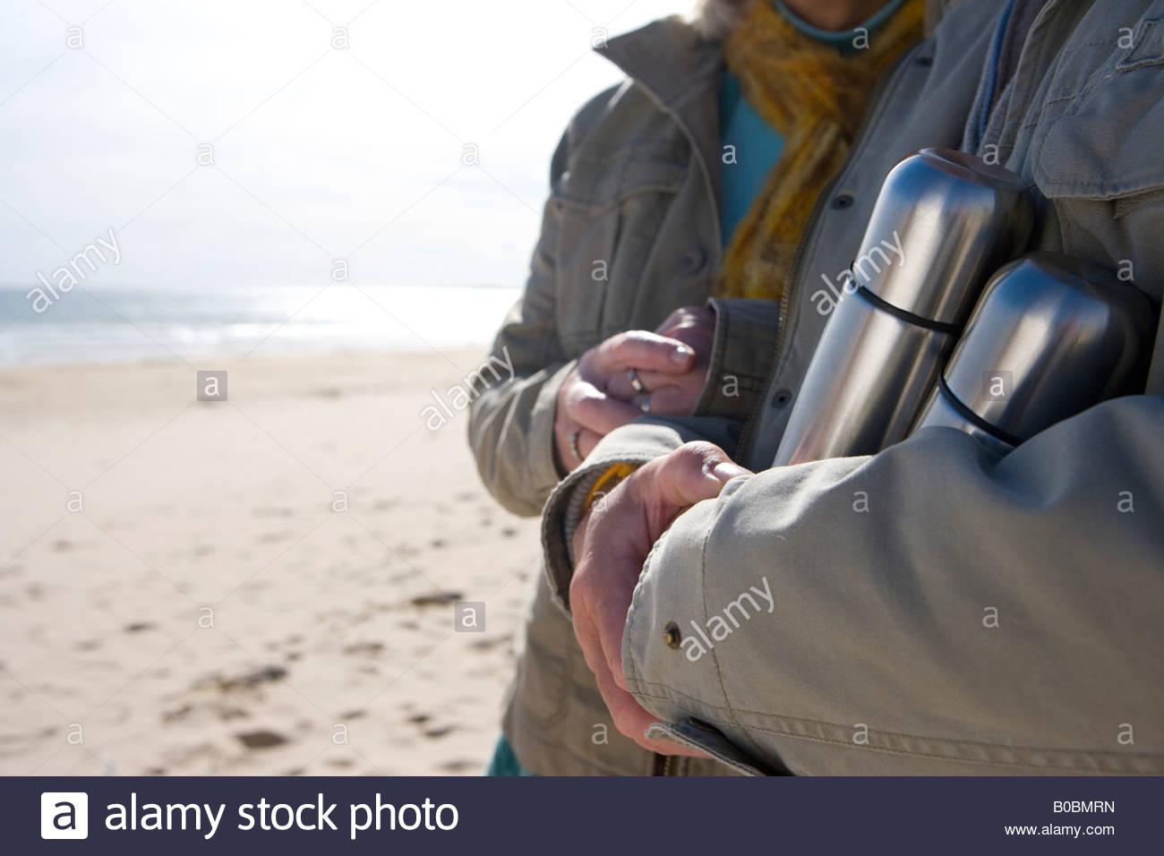 Paar mit isolierten Flaschen am Strand, Mittelteil Stockbild