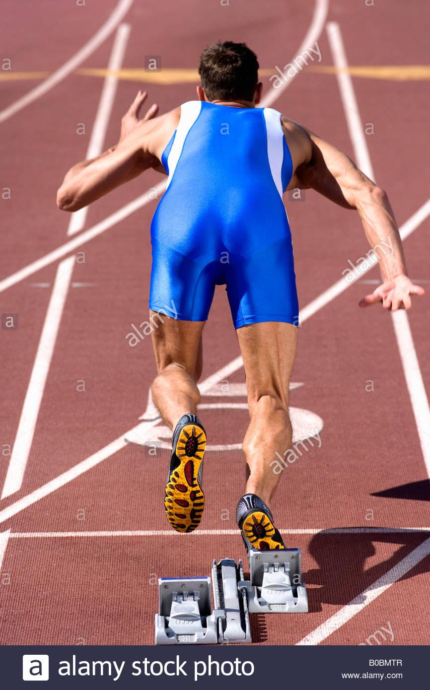 Männlichen Sprinter verlassen Startblock, Rückansicht Stockbild