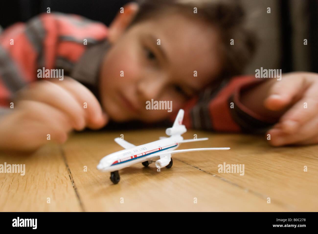 Junge spielt mit einem Spielzeugflugzeug Stockbild