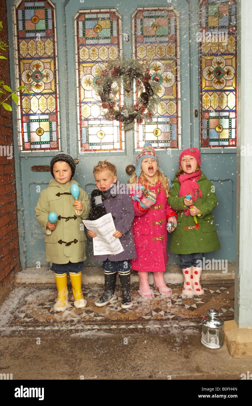 vier Kinder singen Weihnachtslieder im Schnee vor der Haustür von ...