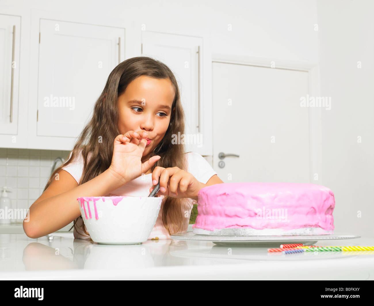 Mädchen lecken Finger von Eistee Kuchen Stockfoto