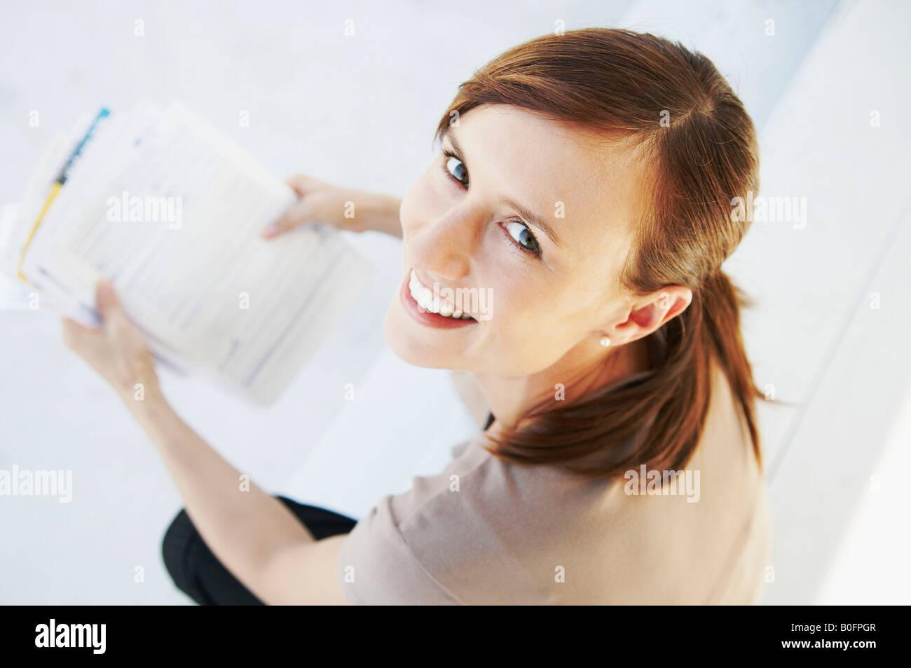 Glückliche Frau schaut vom Papierkram Stockfoto