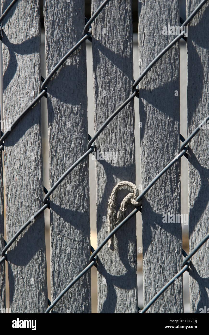 Muster, die durch einen Holzzaun, Kettenglied, ein Stück Seil, Licht ...