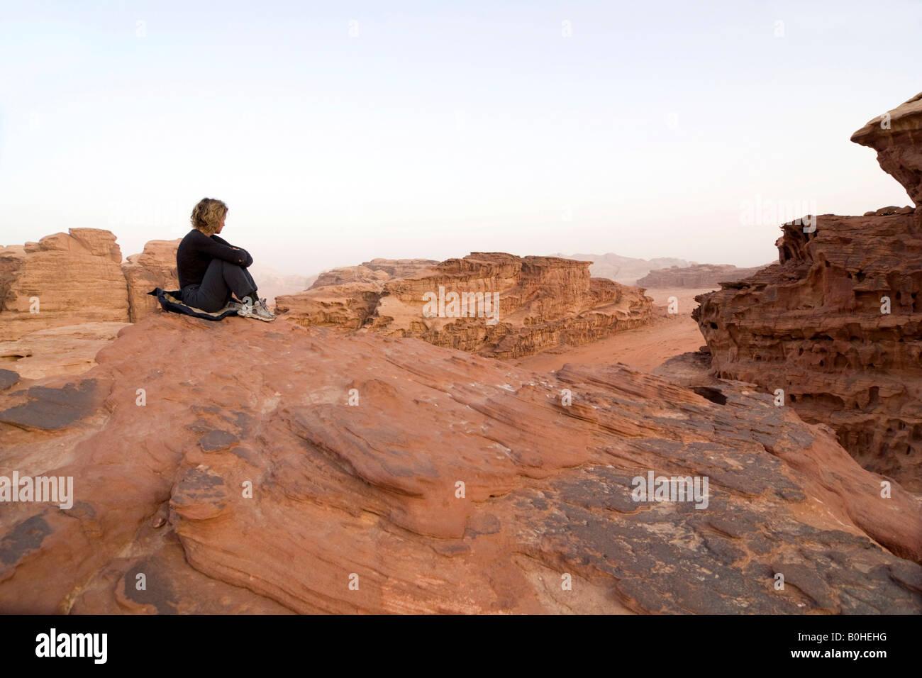 Frau sitzt auf eine Rock Ledge aussehende aus in der Entfernung, Wadi Rum, Jordanien, Naher Osten Stockbild