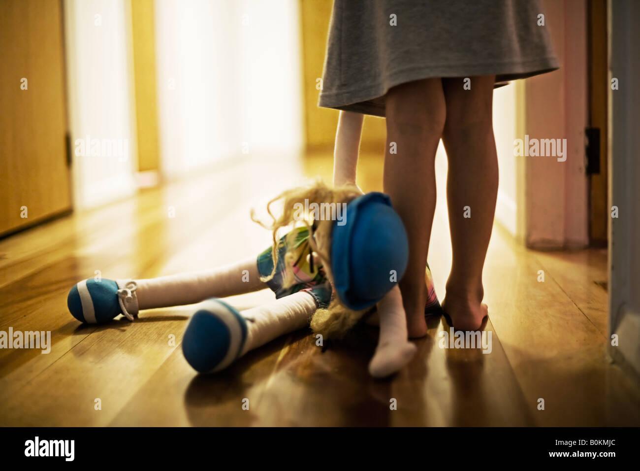 Mädchen im Alter von vier Jahren trägt Spielzeugpuppe in Halle Stockbild