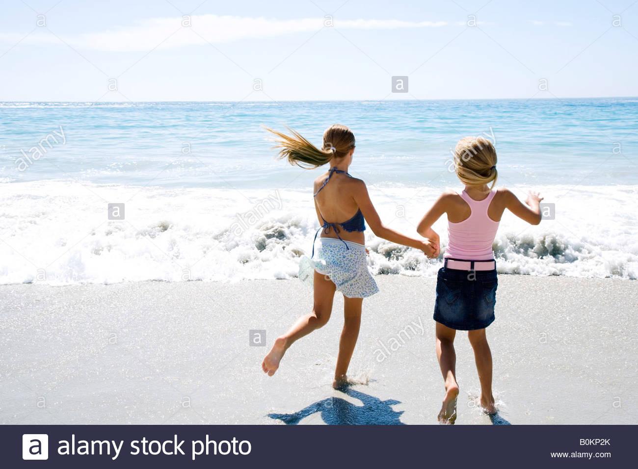 8c067b946f Zwei junge Mädchen am Strand laufen hand in hand Stockfoto, Bild ...