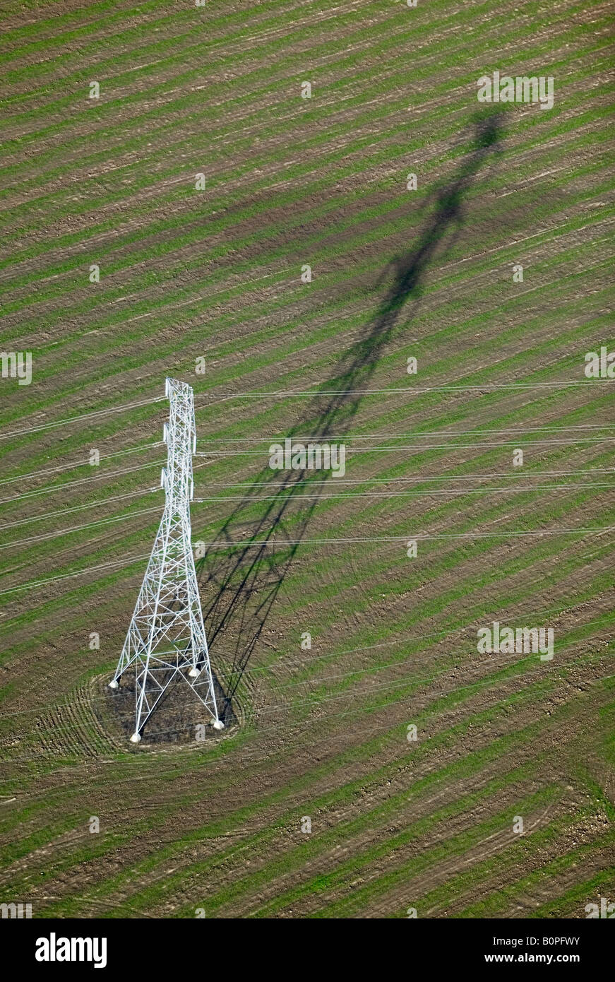 Antenne über ein Strom-Übertragungsleitung wirft einen langen Schatten Stockbild