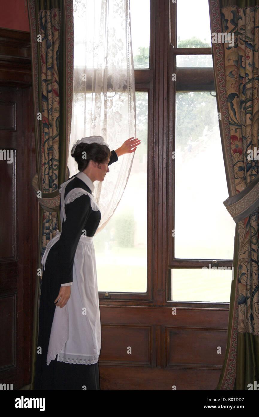 Ein Zimmermädchen blickt aus dem Fenster in einem herrschaftlichen Haus. Stockbild