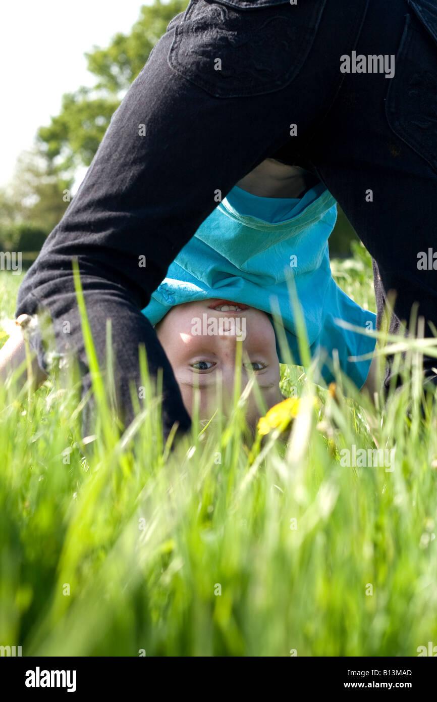 kleiner Junge macht Handstand in Sommerwiese Stockbild