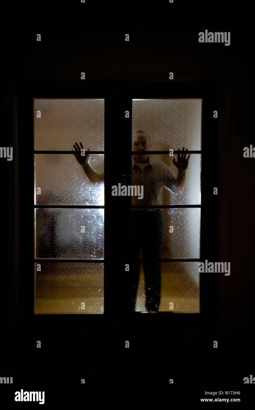 Mann von Doppelglas Innentüren in einem abgedunkelten Raum Stockbild
