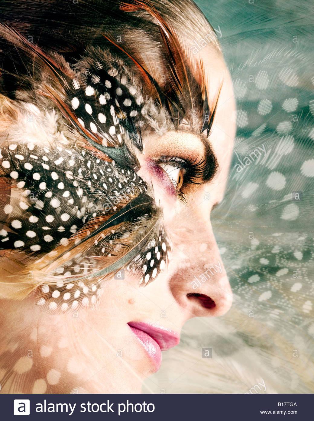 Junge Frau mit Federn um ihre Augen Stockbild