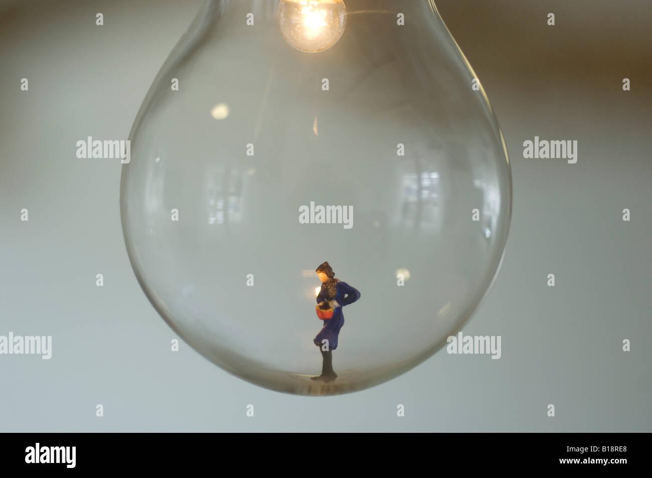 Eine winzige geformte Figur allein in eine Glühbirne mit einem Licht von oben beleuchtet. Stockbild