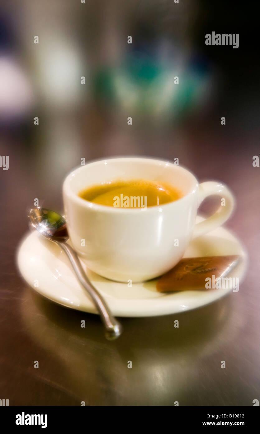 weiße Kaffeetasse mit Espresso auf Küchentisch mit Löffel und ...
