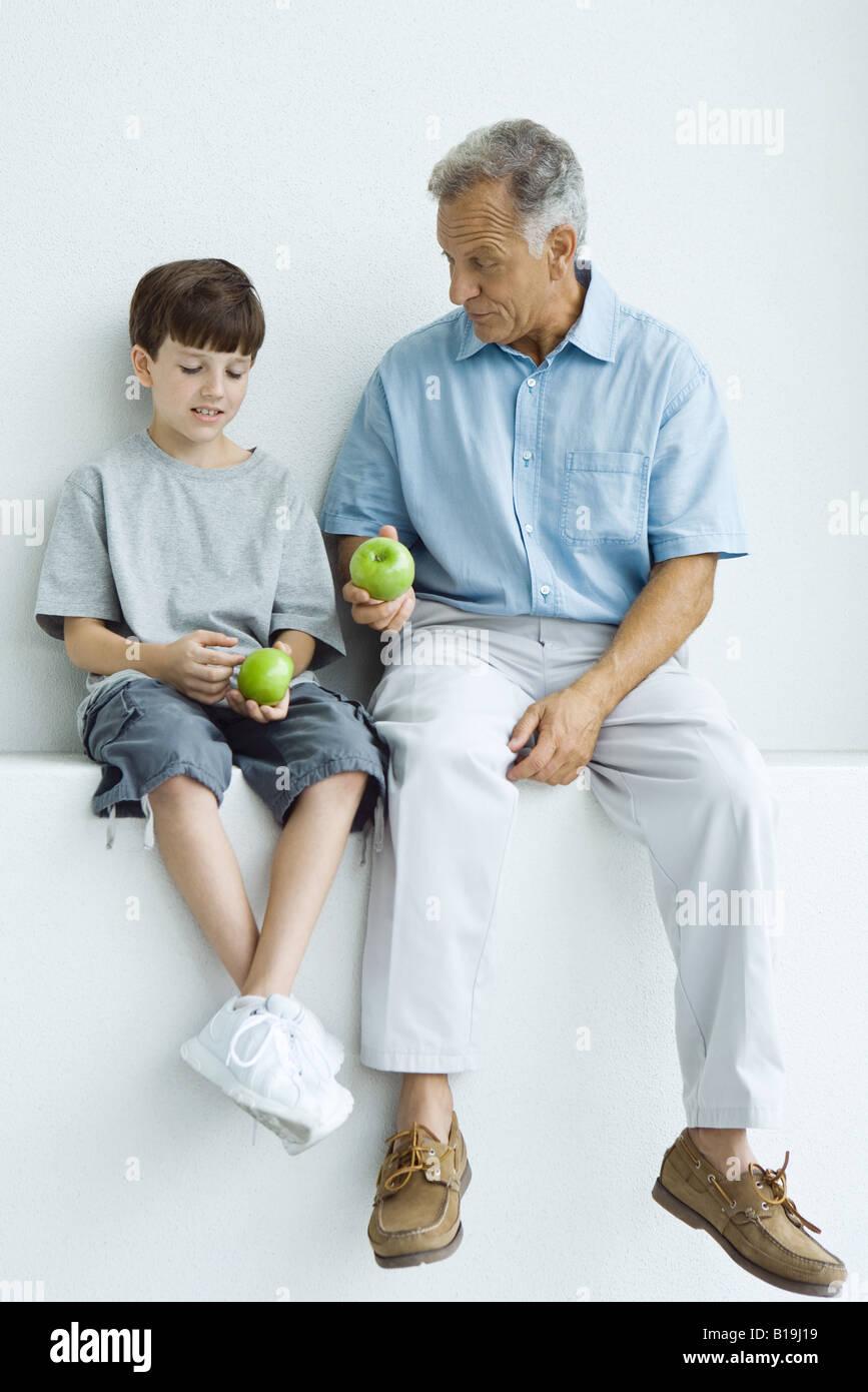 Großvater und Enkel sitzen zusammen auf Felsvorsprung, beide halten Äpfel Stockbild