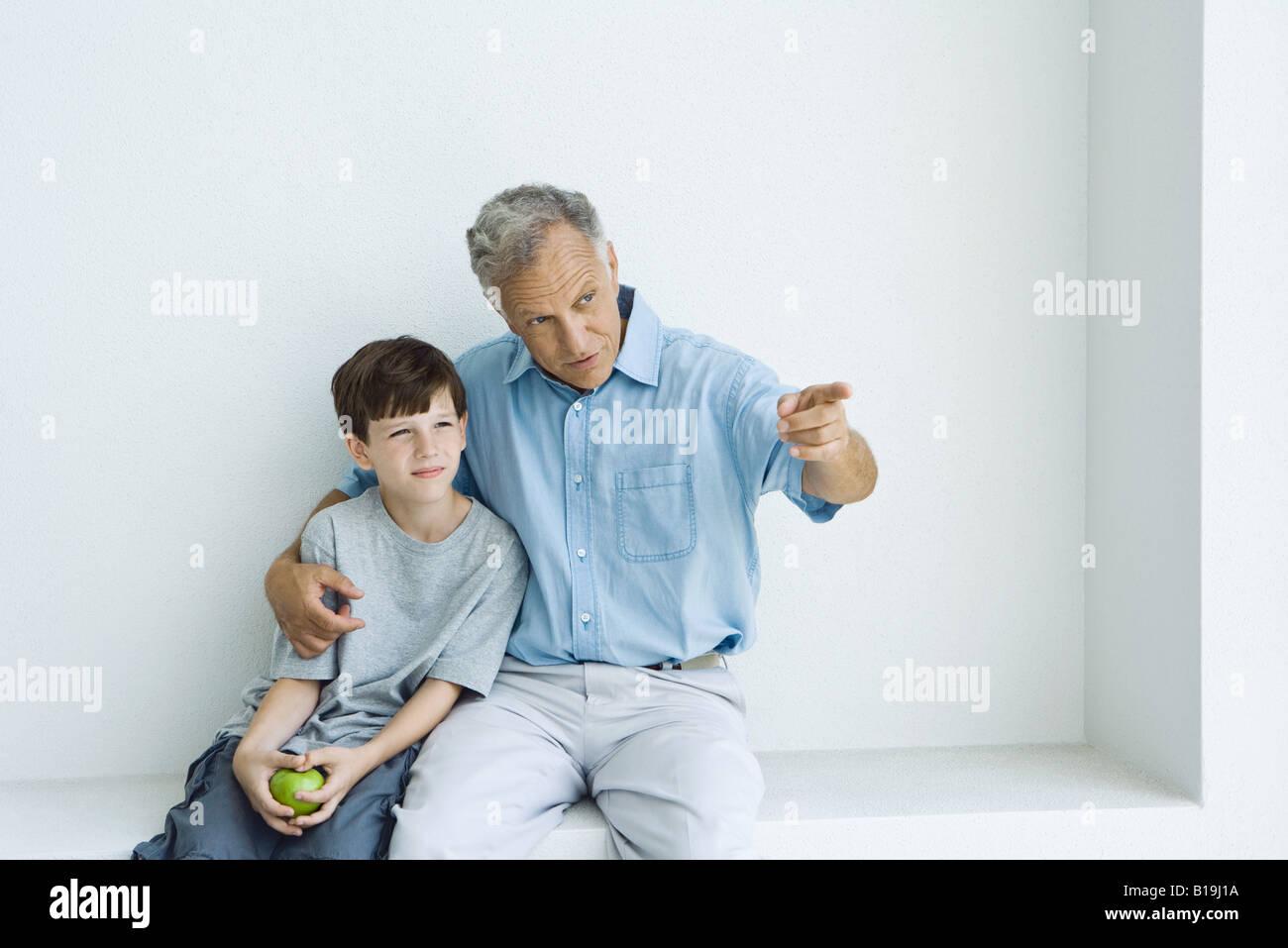 Großvater und Enkel zusammensitzen, Mann zeigte, junge hält Apfel Stockbild