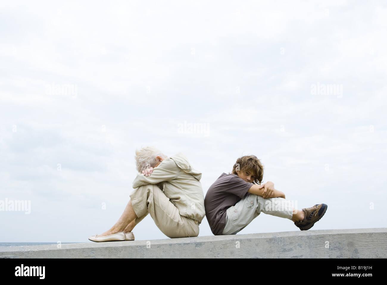 Großmutter und Enkel sitzen Rücken an Rücken, Kopf, Arme verschränkt, junge Blick in die Kamera Stockbild