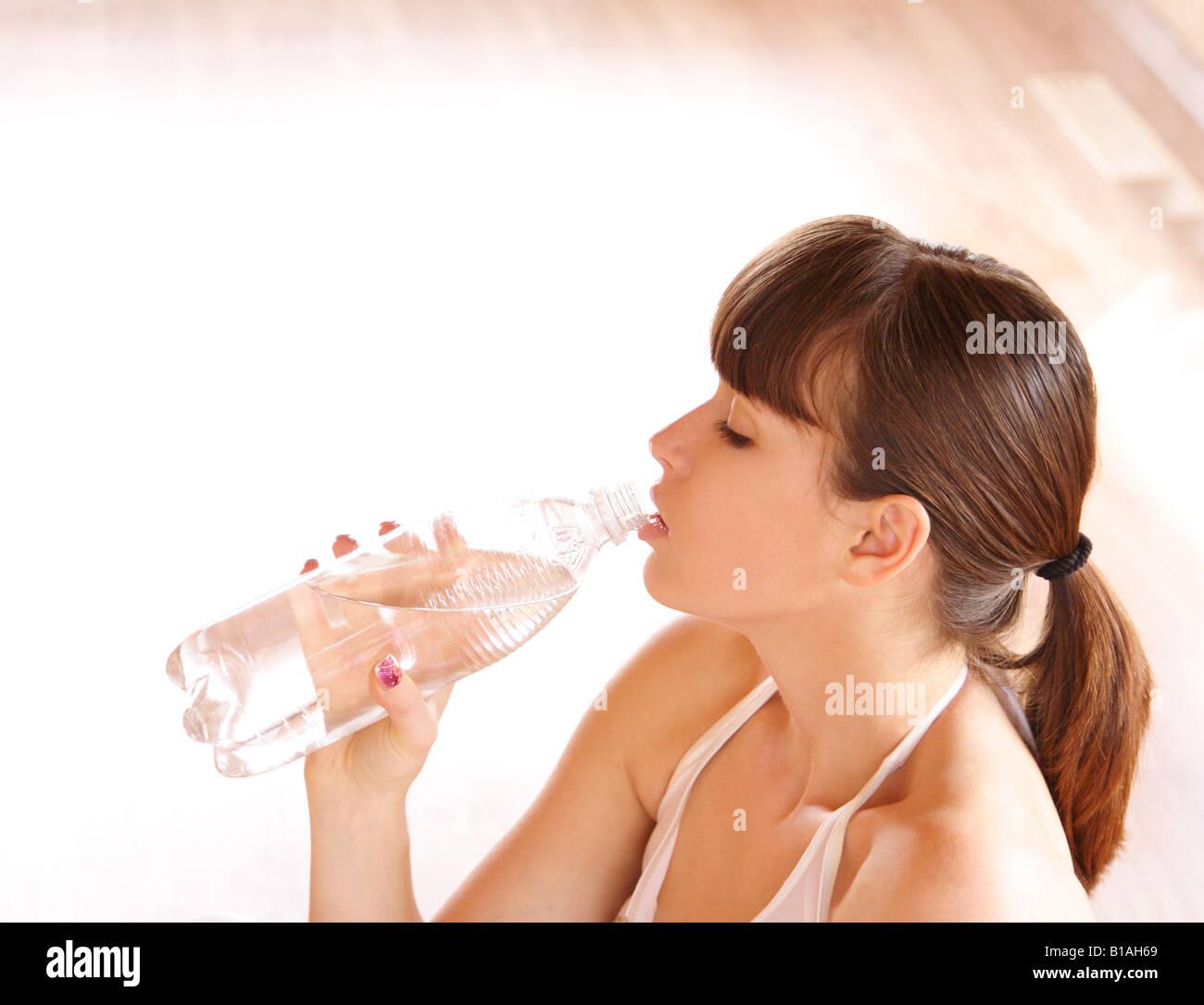 Junge Frau Trinkwasser nach dem training Stockbild