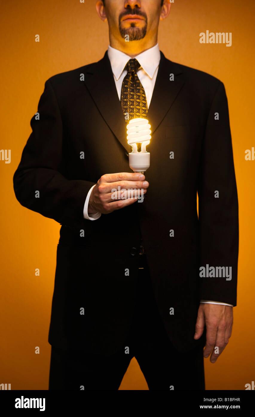 Kaukasische Geschäftsmann im Anzug steht eine beleuchtete kompakte Leuchtstofflampen-Glühbirne in der Stockbild