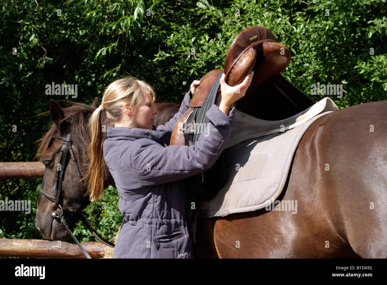 Frau platzieren Sattel auf ihrem Pony satteln ihr Haustier pony Stockbild