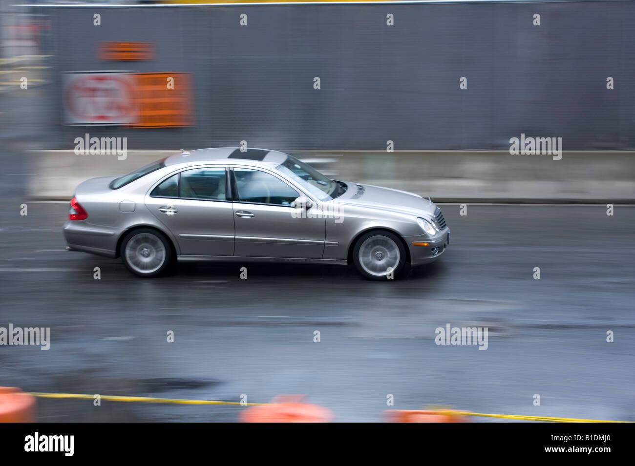 Eine Mercedes-Limousine beschleunigt in einer Straße in Manhattan, New York an einem regnerischen Tag. Stockfoto