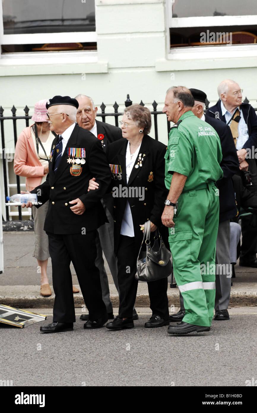 Sanitäter, hilft einen alten Soldat, der ein bisschen fühlte unsteady an den Füßen bei einer Stockbild