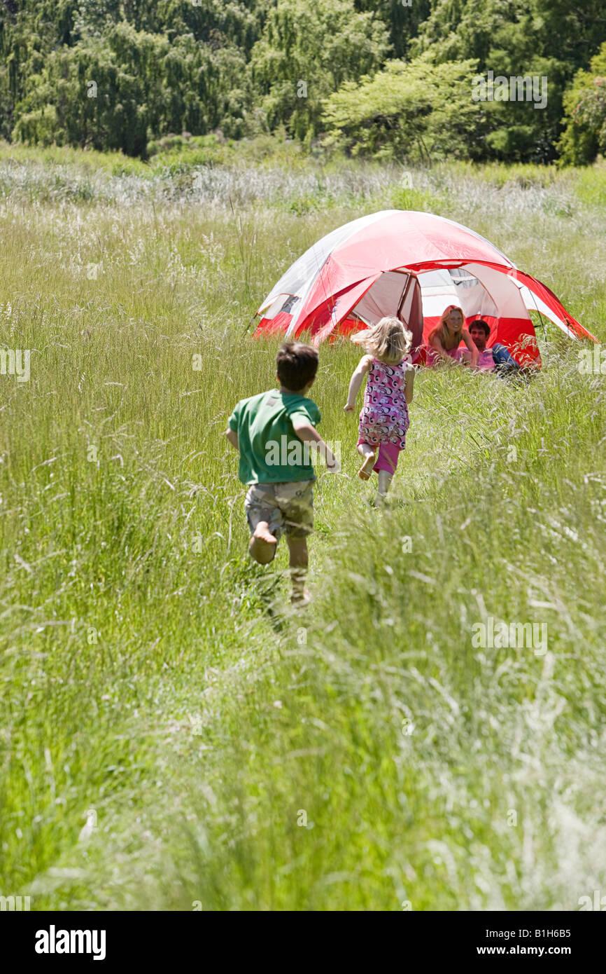 Kinder laufen mit ihren Eltern Stockbild