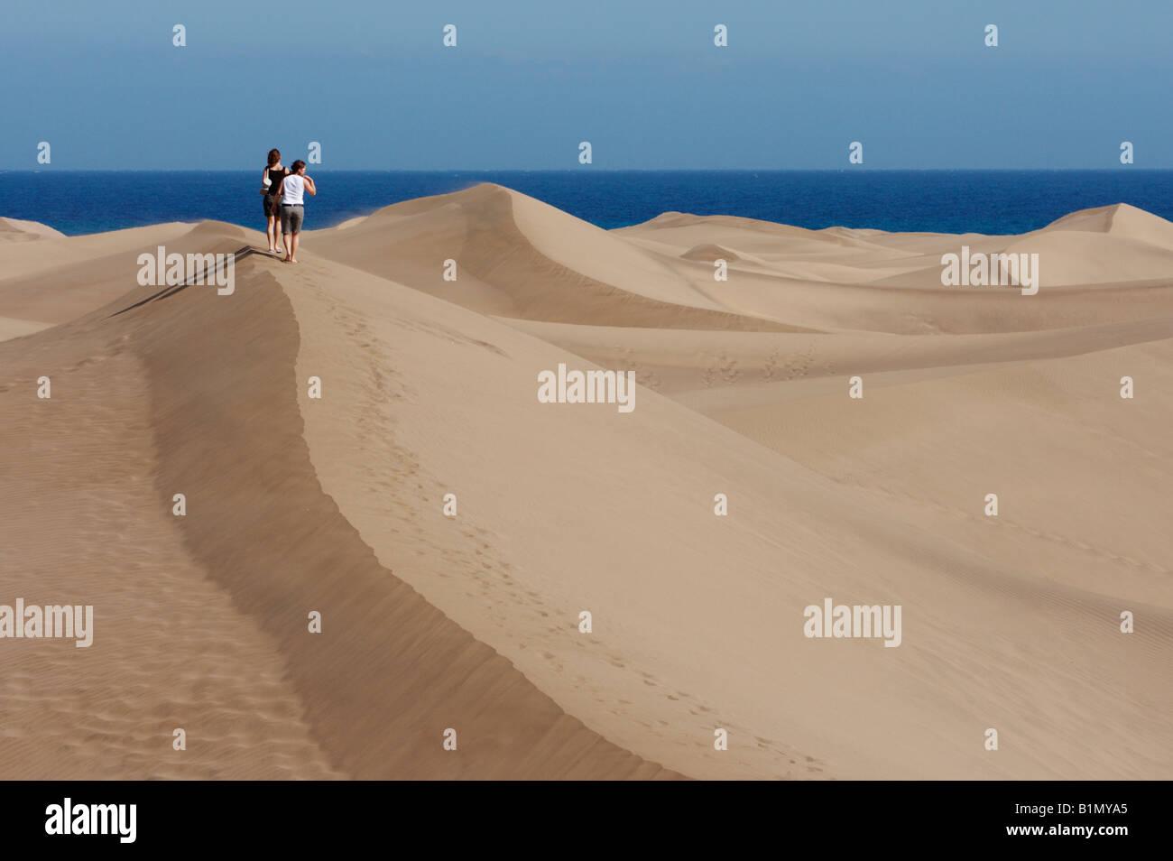 Zwei junge Frauen, die zu Fuß in die Dünen in Maspalomas auf Gran Canaria auf den Kanarischen Inseln. Stockfoto