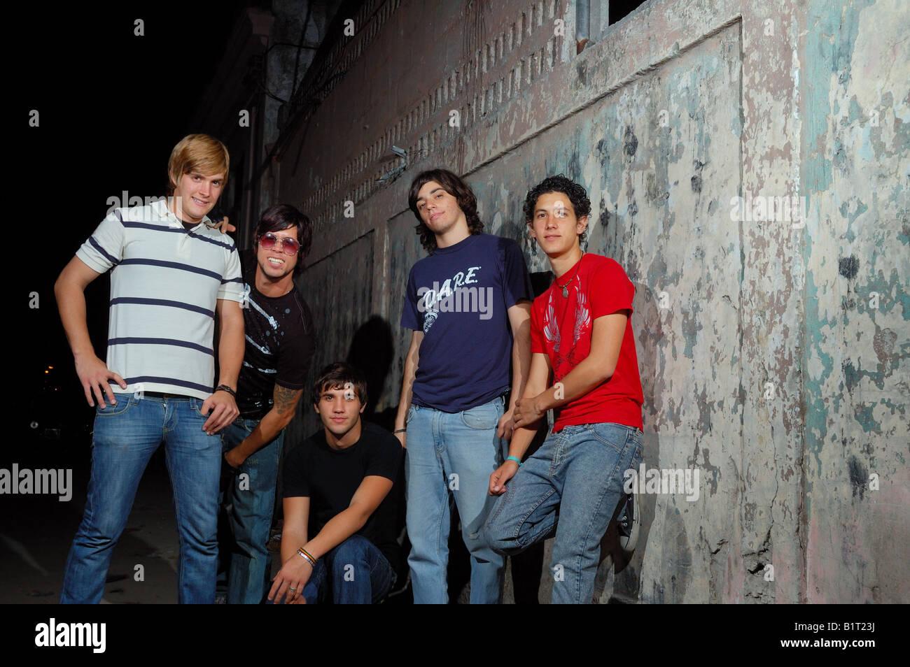 Lockere Gruppe von Jugendlichen gegen Grunge Wand stehend Stockbild