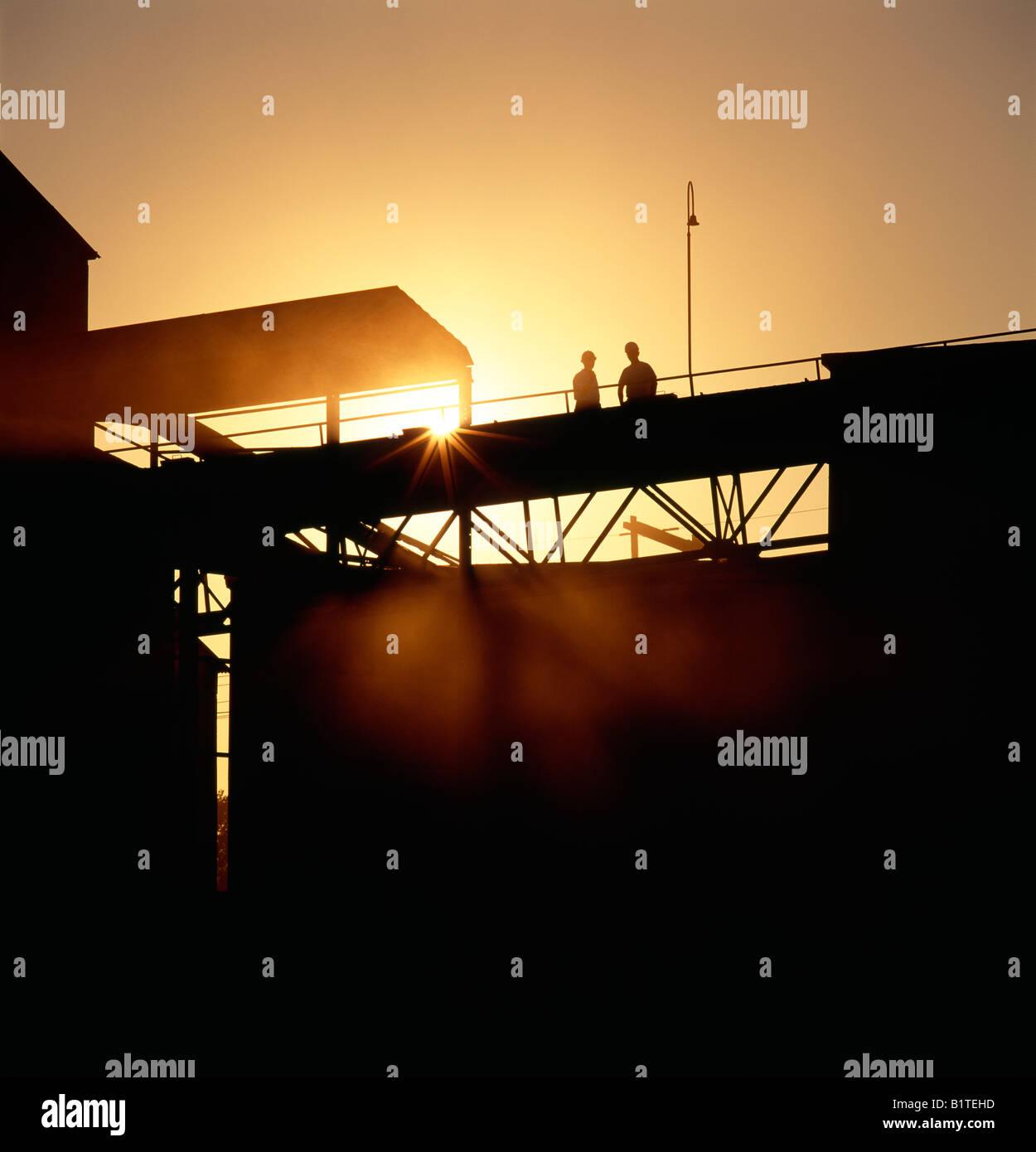 Arbeitnehmer, die Silhouette gegen den Sonnenaufgang an einem Zementwerk. Stockbild