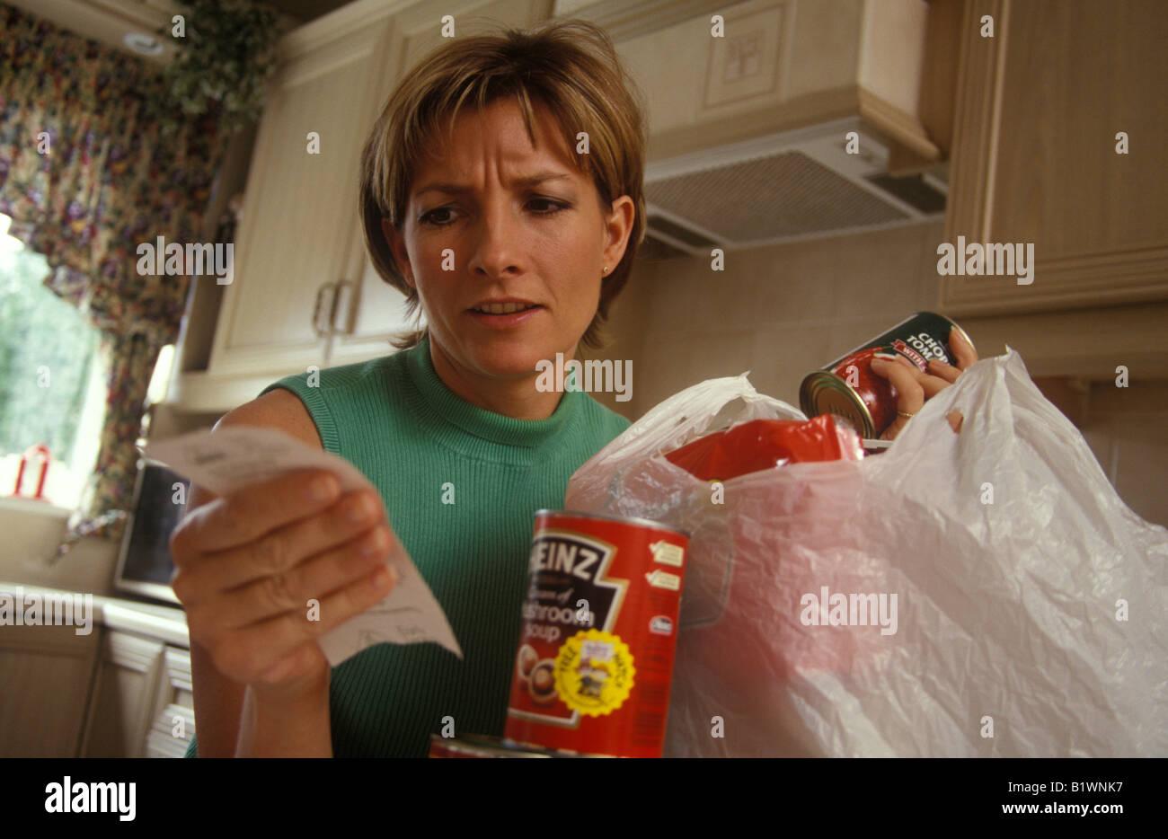 010c3e1e80 Frau verzweifelt ihr Einkaufen Auspacken und auf der Suche über Preise  Stockbild