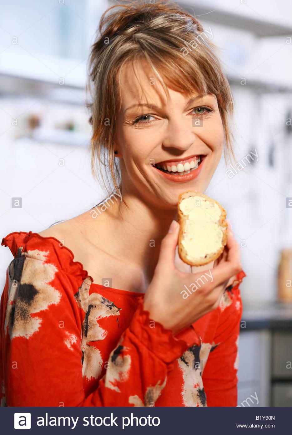 Frau Brot essen Stockbild