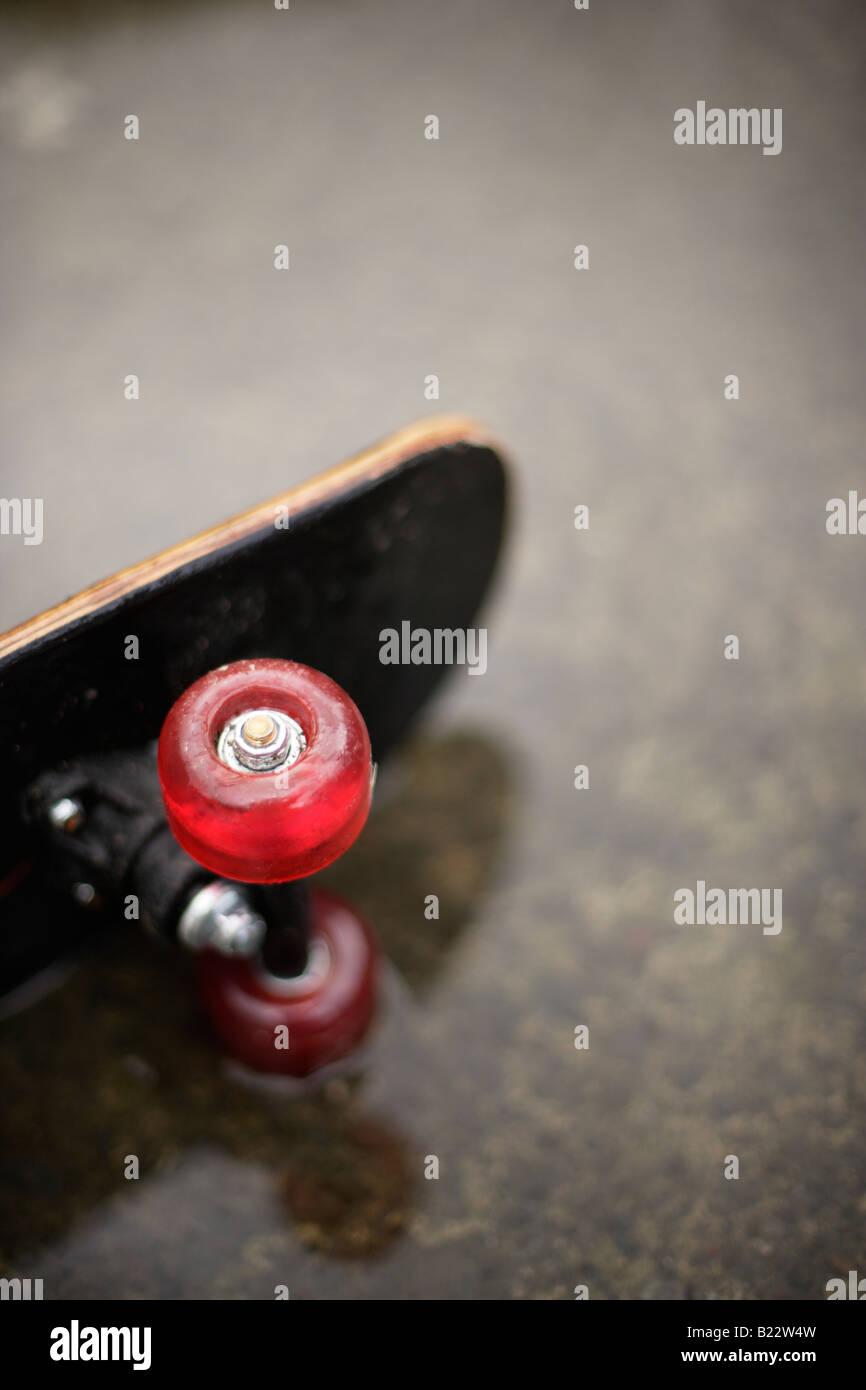 Skateboard in Pfütze Stockbild