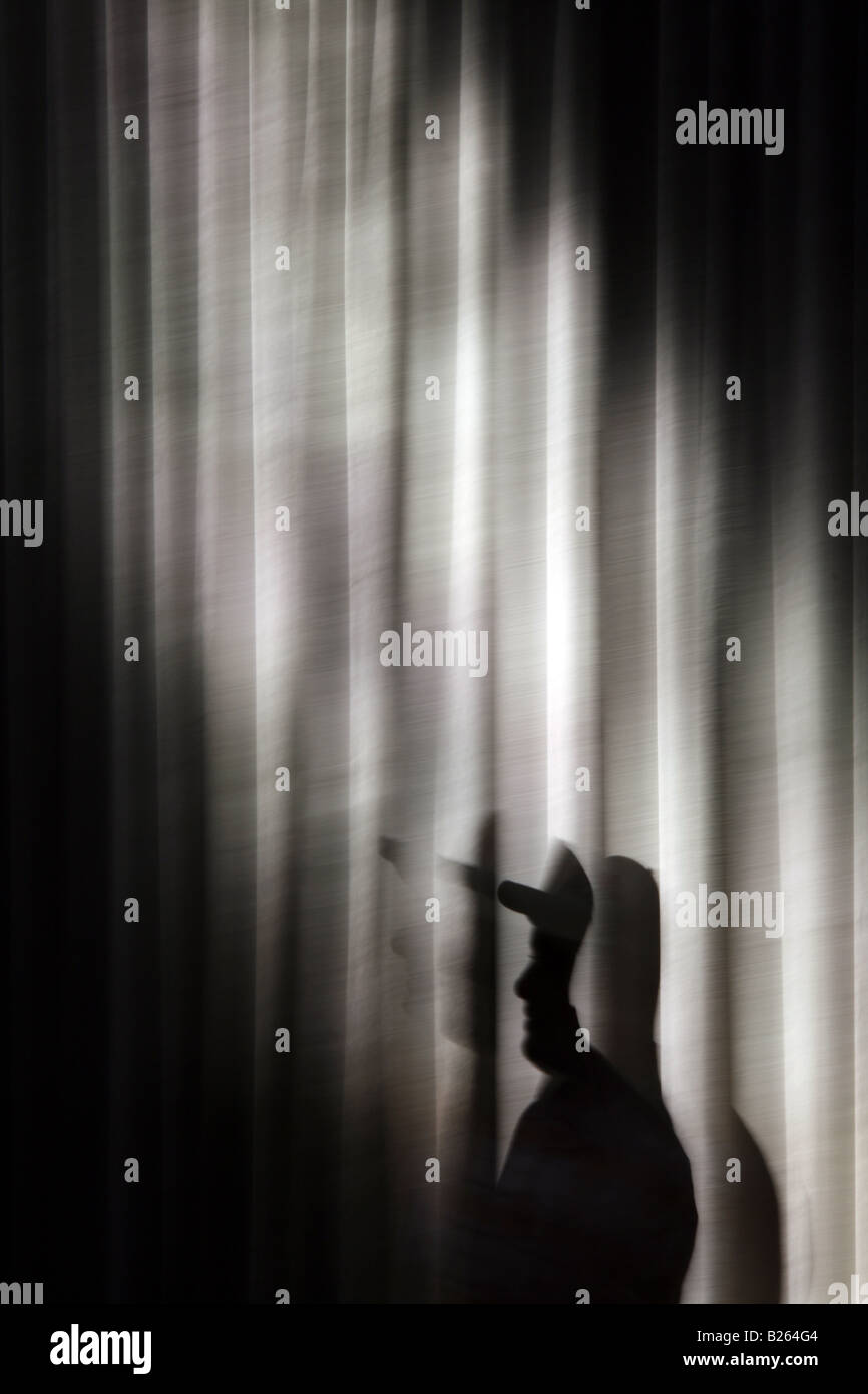 Person und lange dunkle Vorhänge Vorhänge im Zimmer Stockbild