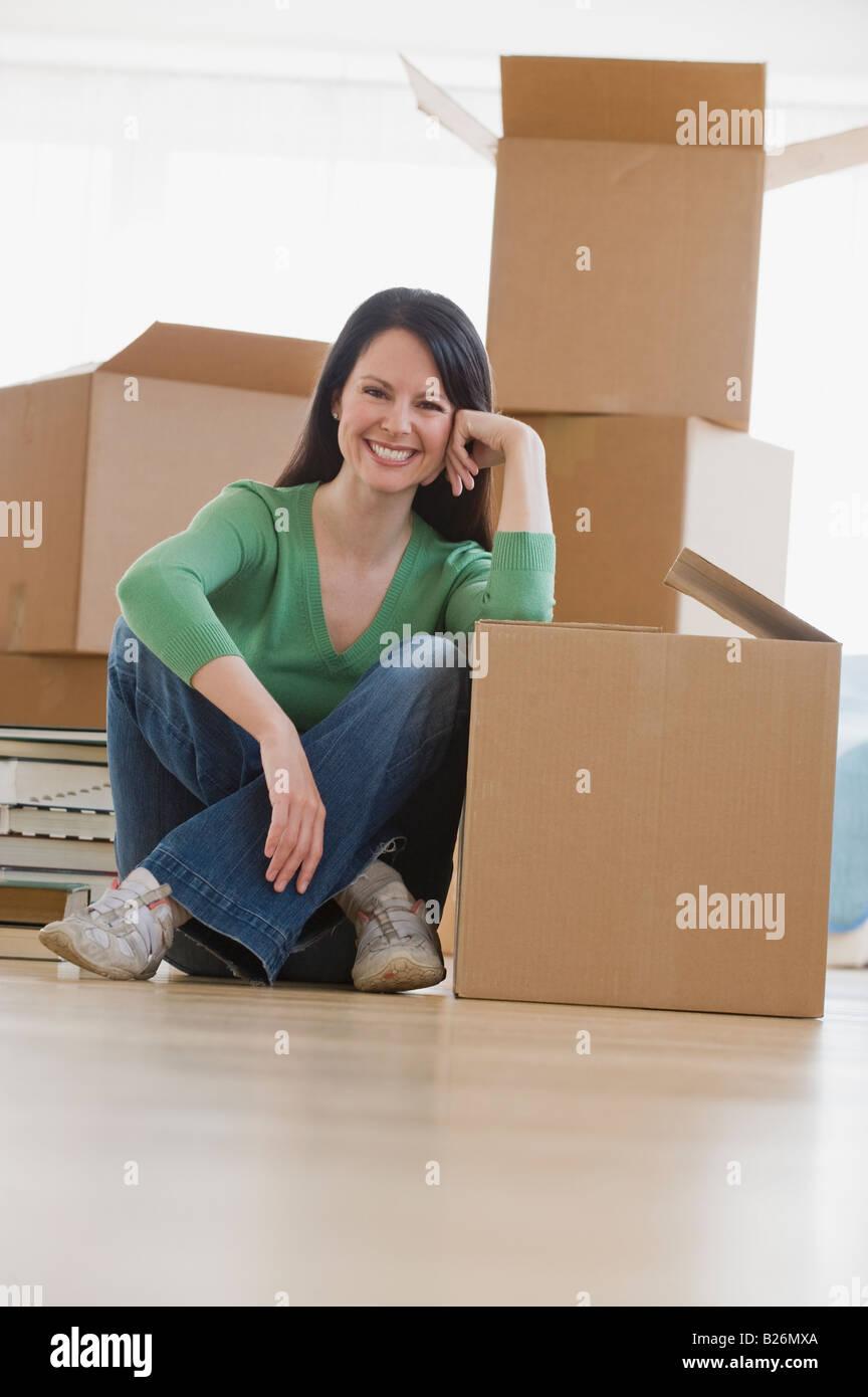 Frau lehnt sich auf beweglichen Box im neuen Haus Stockbild
