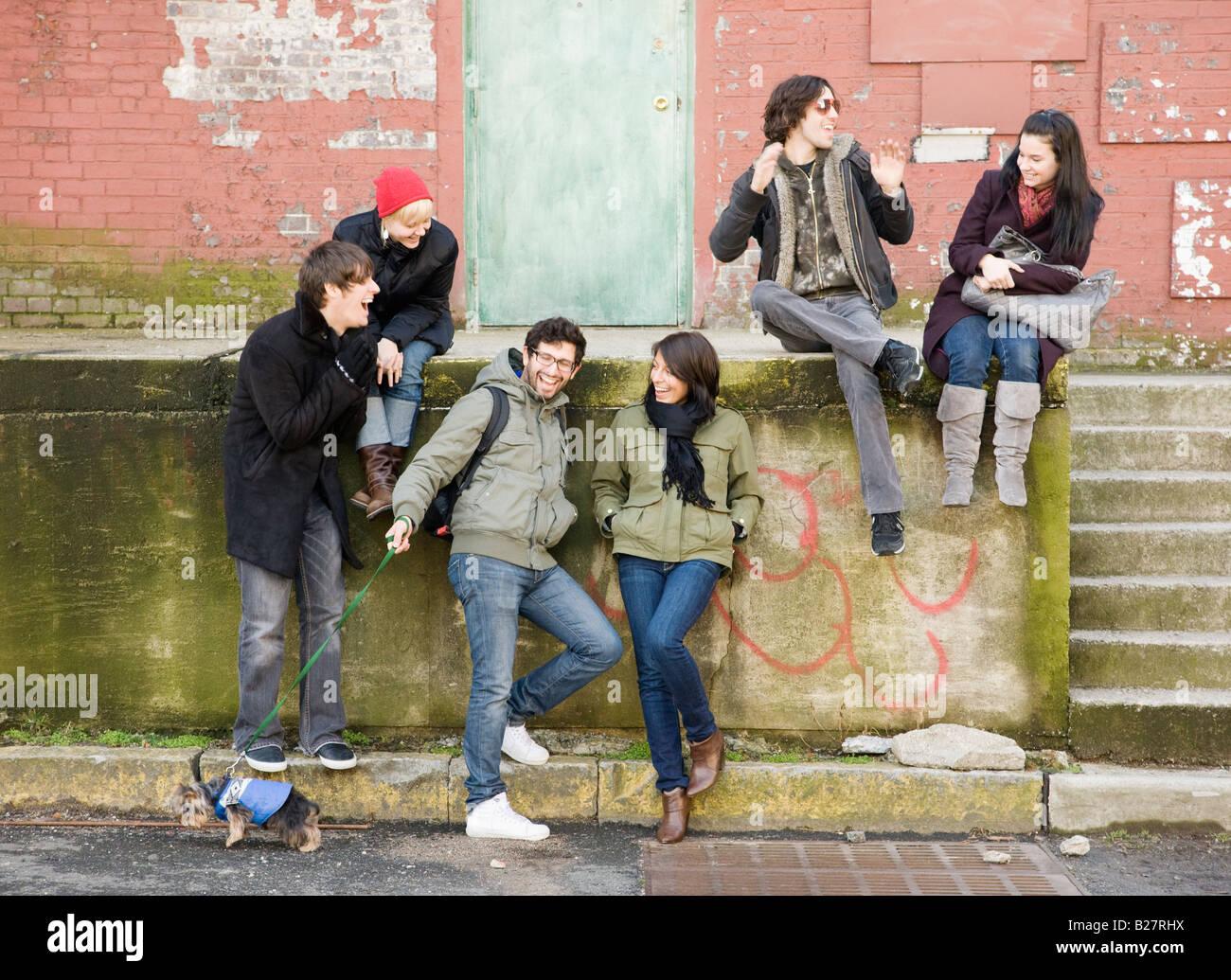 Gruppe von Freunden sitzen in städtischen Szene Stockbild