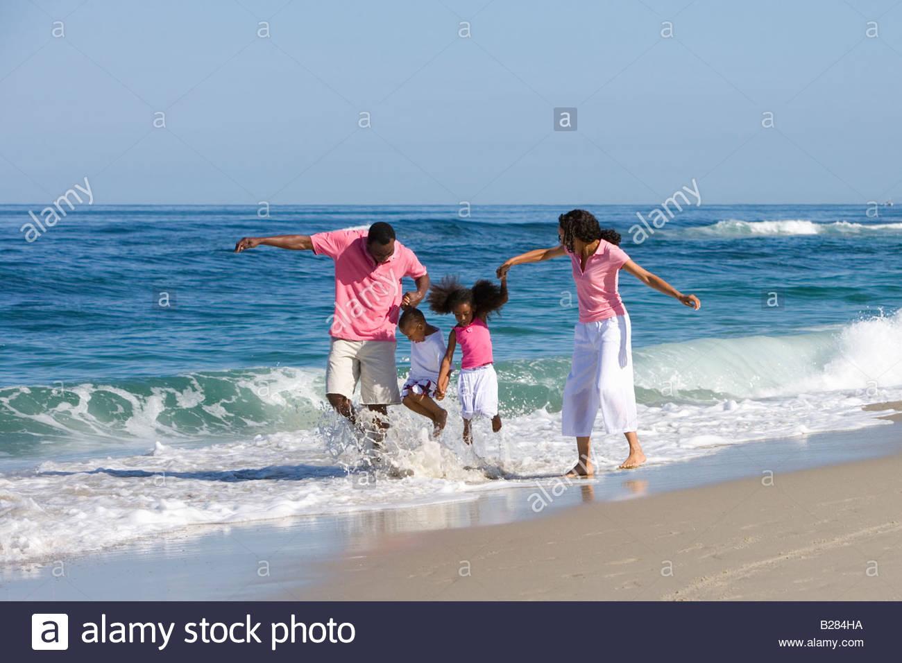 Vierköpfige Familie Wandern in Wellen am Strand Stockfoto