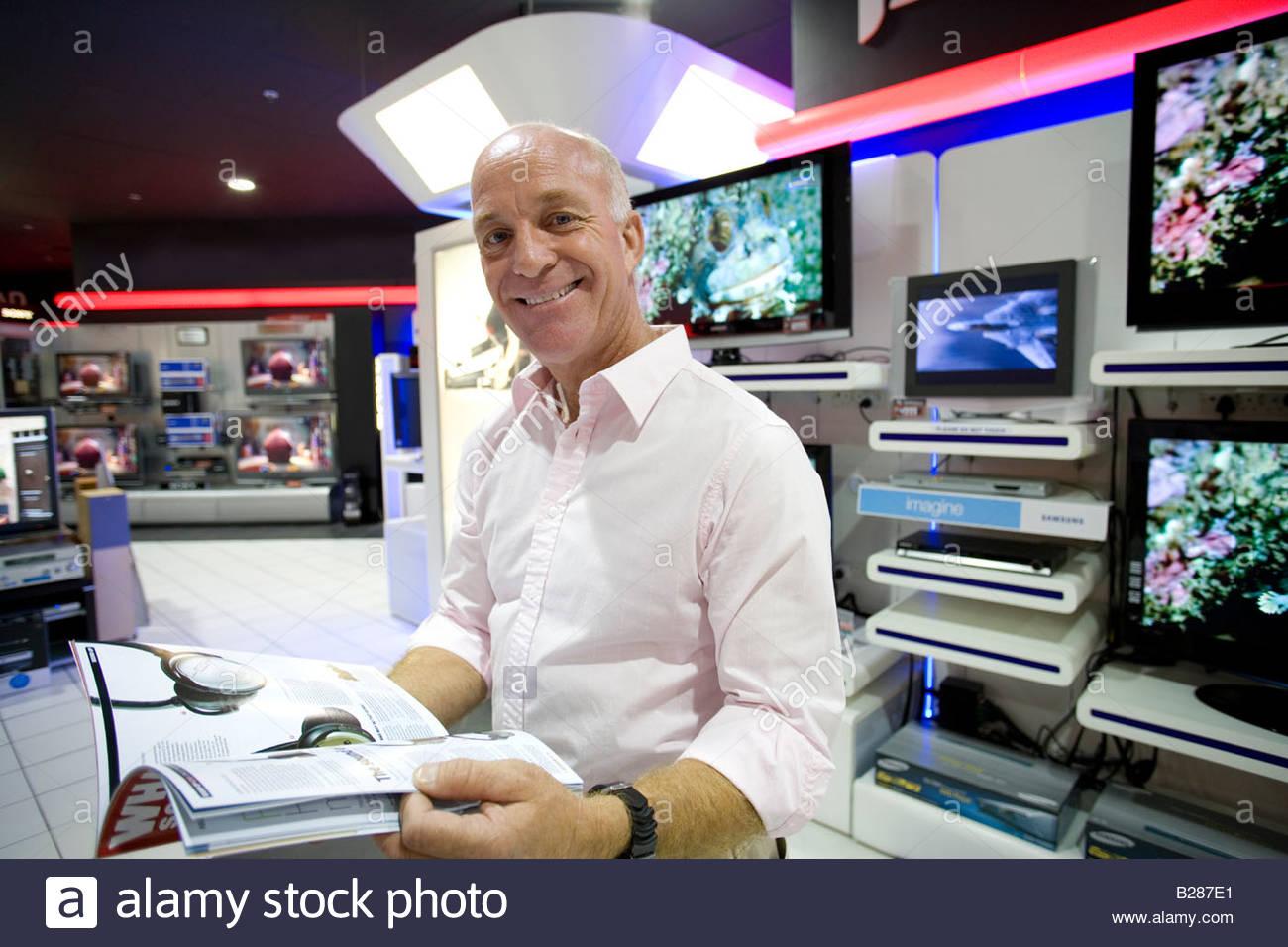 Mann mit Katalog im Elektronik-Geschäft, Lächeln, Porträt Stockbild
