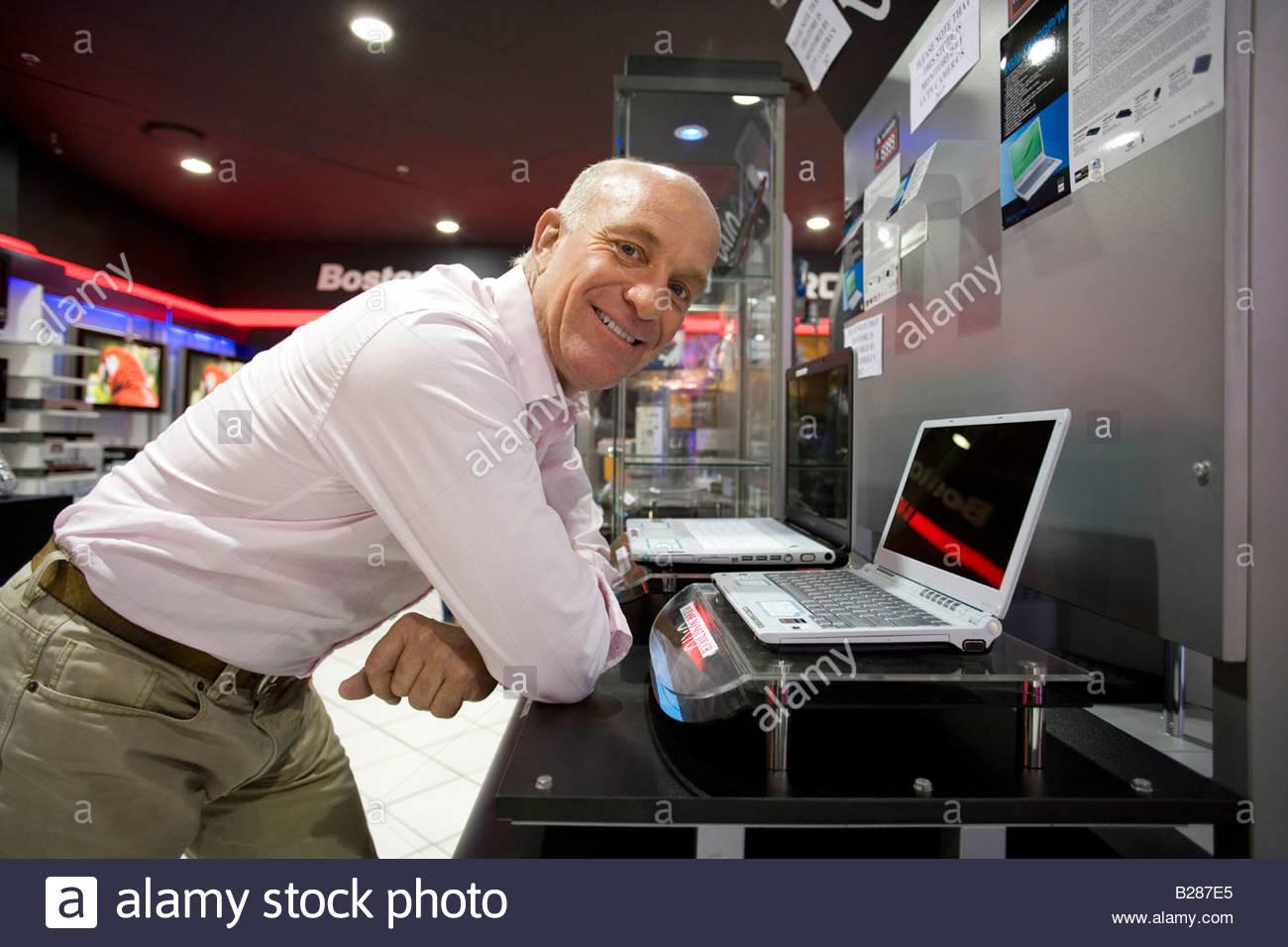 Mann mit Laptop-Computer im Elektronik-Geschäft, Lächeln, Porträt Stockbild