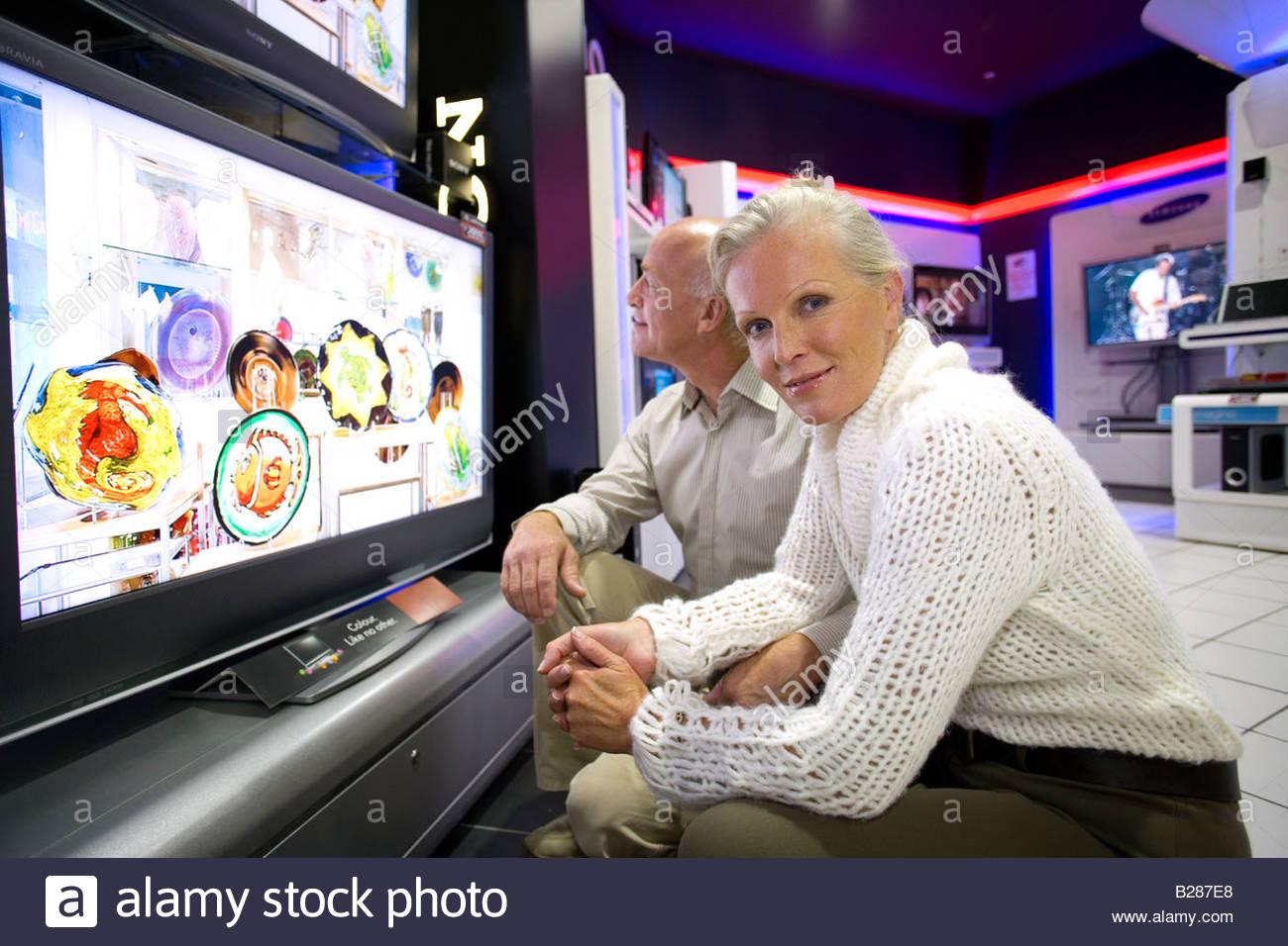 Älteres Paar mit Flachbildschirm im Elektronik-Shop, Portrait Frau Stockbild