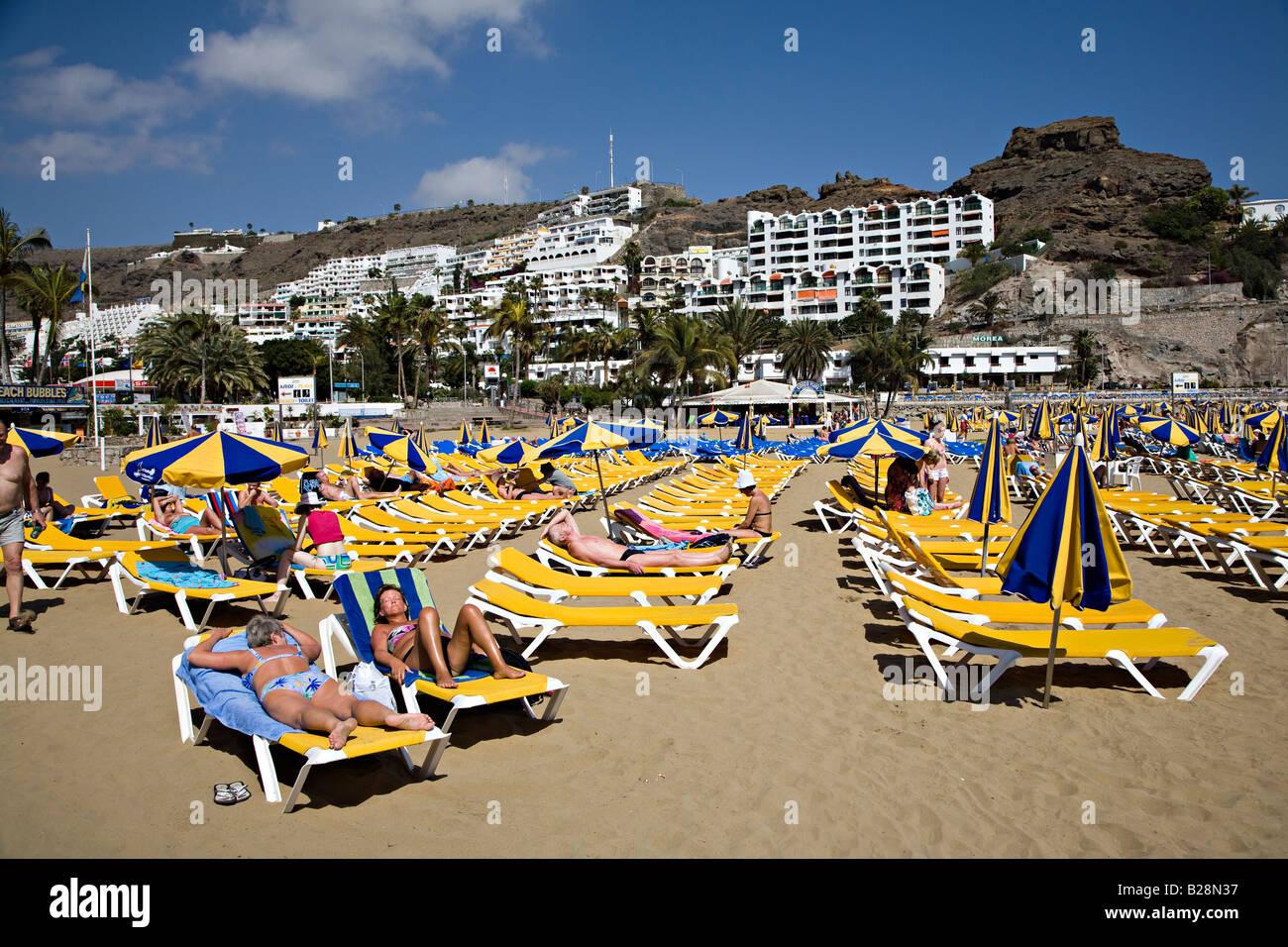 Menschen am Strand liegen mit Resort Ferienwohnungen auf Hügel Puerto Rico Gran Canaria Spanien Stockbild