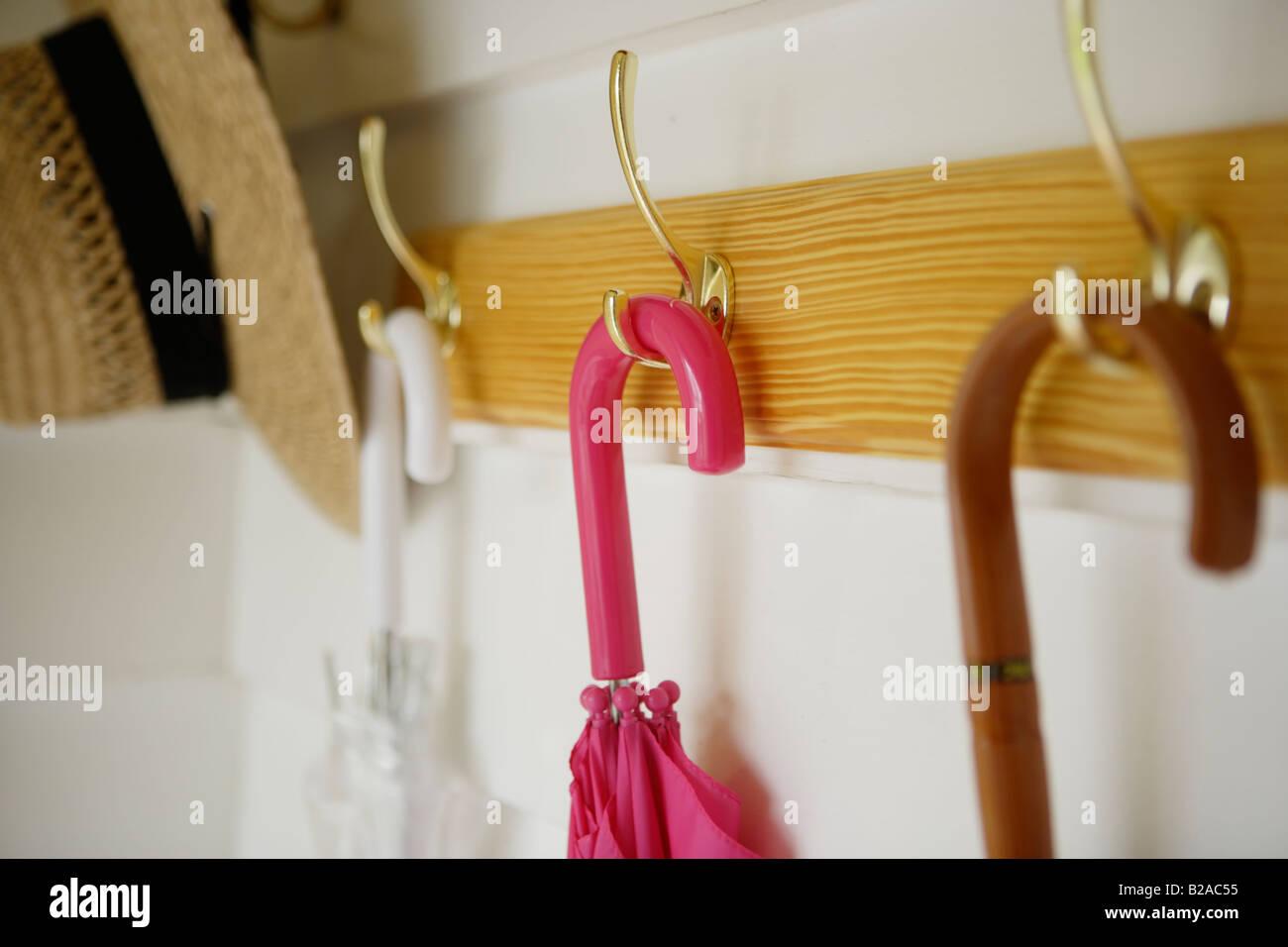 Sonnenschirme und Strohhut von Kleiderständer hängen Stockbild