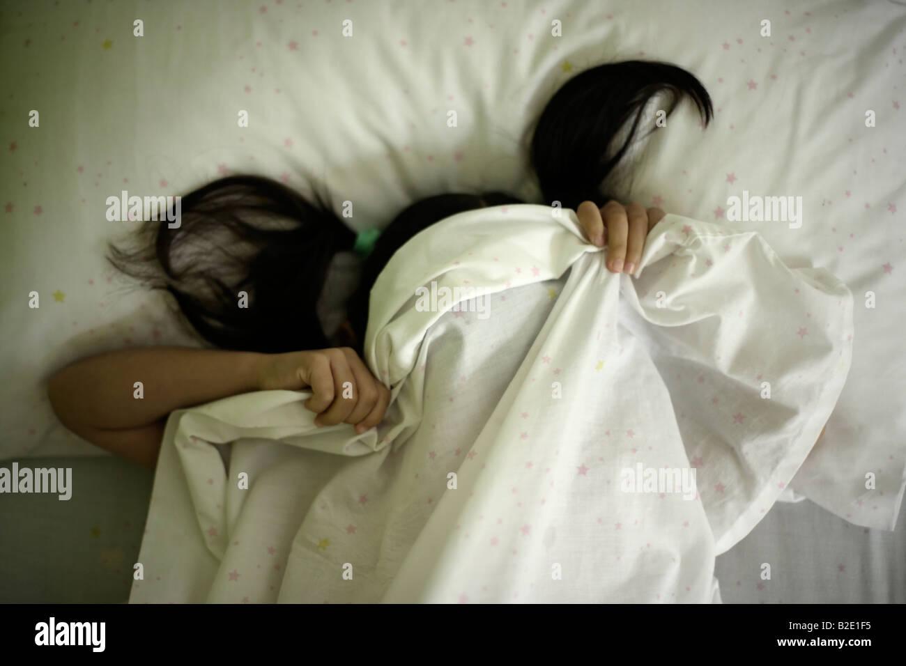 Fünf Jahre altes Mädchen versteckt sich unter Blätter nach Wutanfall Stockfoto